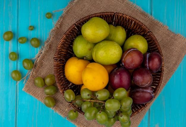 Vista superior de frutas como nectacotes de plumagem de uva na cesta e bagas de uva em tecido xadrez e sobre fundo azul