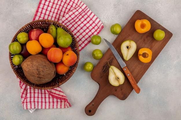 Vista superior de frutas como pera e damasco cortados pela metade com faca na tábua e cesta de coco, pêssego, ameixa, pêra em tecido xadrez e ameixas em fundo branco