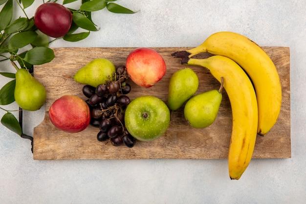 Vista superior de frutas como pêra, maçã, pêssego, banana, numa tábua, com folhas no fundo branco