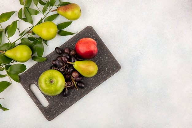 Vista superior de frutas como pêra, maçã, uva, pêssego, numa tábua, com folhas em fundo branco com espaço de cópia