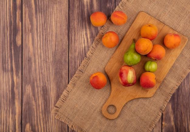 Vista superior de frutas como pêssego, ameixa, pera, damasco, na tábua e no saco em fundo de madeira com espaço de cópia