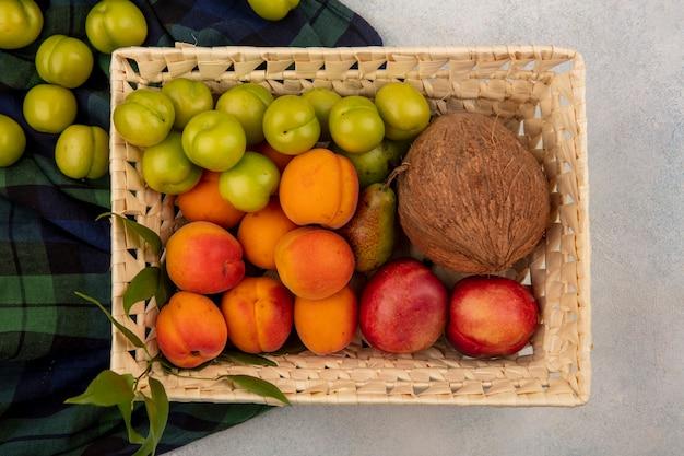 Vista superior de frutas como pêssego, damasco, ameixa, coco, pera em uma cesta em tecido xadrez e fundo branco