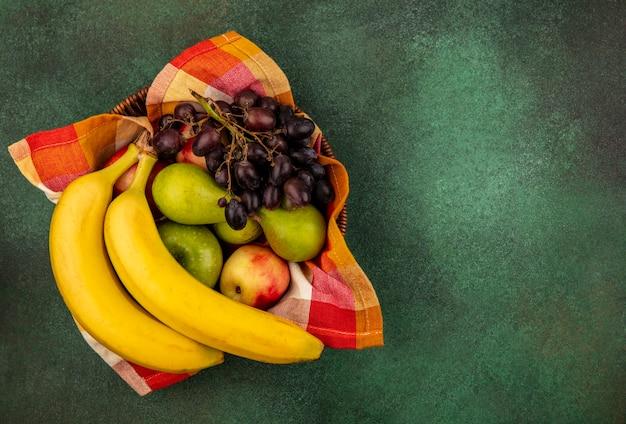 Vista superior de frutas como pêssego, maçã, pêra, banana, uva, cesta, sobre fundo verde, com espaço de cópia