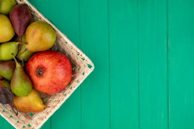 Vista superior de frutas como romã e pêssego na cesta na superfície verde com espaço de cópia