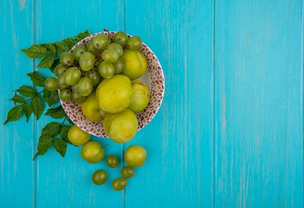 Vista superior de frutas como uva e plumas verdes em uma tigela com ameixas, bagas de uva e folhas em fundo azul com espaço de cópia