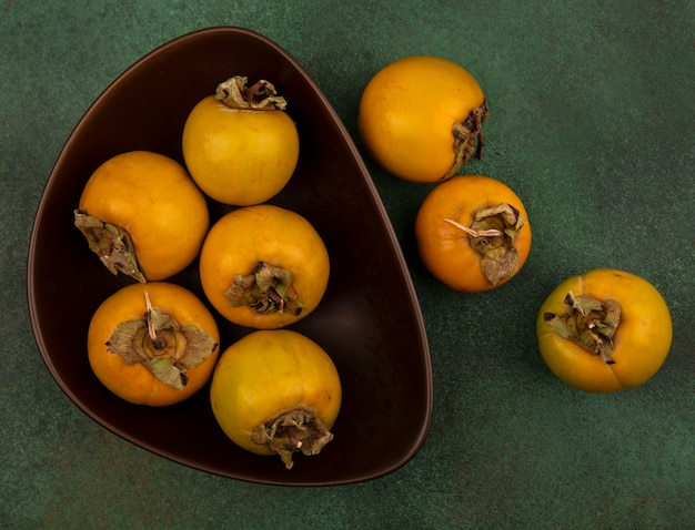 Vista superior de frutas de caqui cheias de nutrientes em uma tigela sobre uma superfície verde