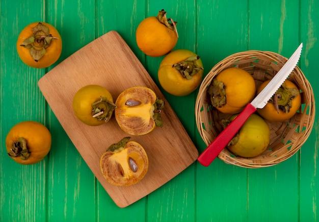 Vista superior de frutas de caqui frescas em um balde com faca com frutas de caqui divididas ao meio em uma placa de cozinha de madeira em uma mesa de madeira verde