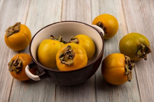 Vista superior de frutas de caqui orgânico laranja em uma tigela sobre uma mesa de madeira cinza