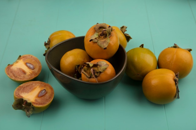 Vista superior de frutas de caqui verde laranja em uma tigela com frutas de caqui isoladas em uma mesa de madeira azul
