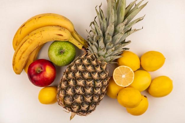 Vista superior de frutas deliciosas, como banana, abacaxi, maçã colorida e limões isolados em uma parede branca