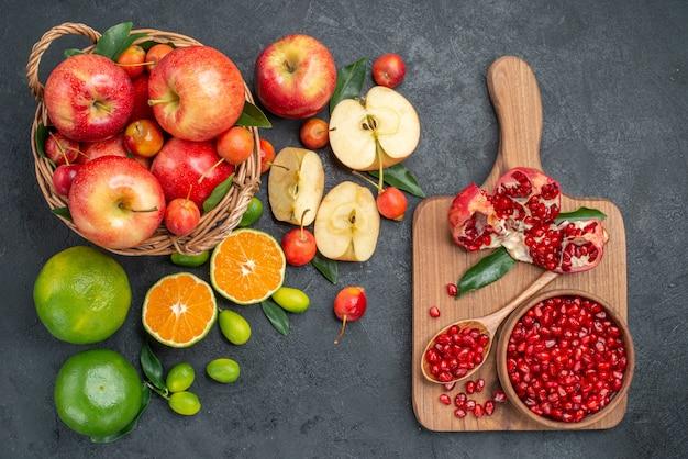 Vista superior de frutas diferentes frutas ao lado do tabuleiro com sementes de romã