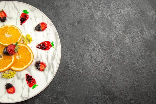 Vista superior de frutas distantes no prato de fatias de frutas cítricas e morangos com cobertura de chocolate na mesa preta