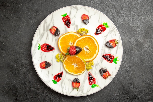 Vista superior de frutas distantes no prato prato branco de frutas cítricas e morangos cobertos de chocolate na mesa preta