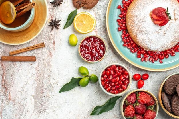 Vista superior de frutas e biscoitos, uma xícara de chá com geleia de limão, biscoitos de chocolate e bolo
