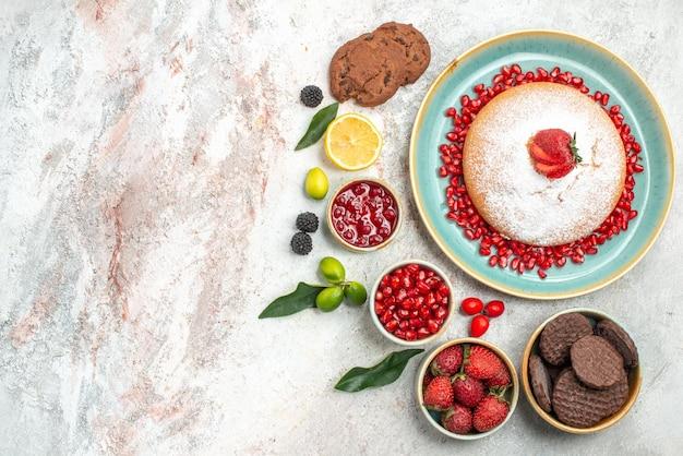Vista superior de frutas e biscoitos, uma xícara de chá preto com biscoitos e bolo de chocolate com geleia de limão