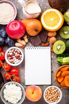 Vista superior de frutas e legumes com caderno em branco