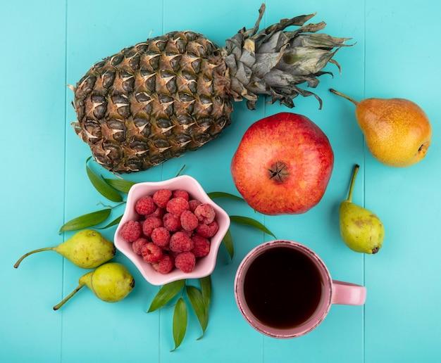 Vista superior de frutas e tigela de framboesa com uma xícara de chá e folhas na superfície azul