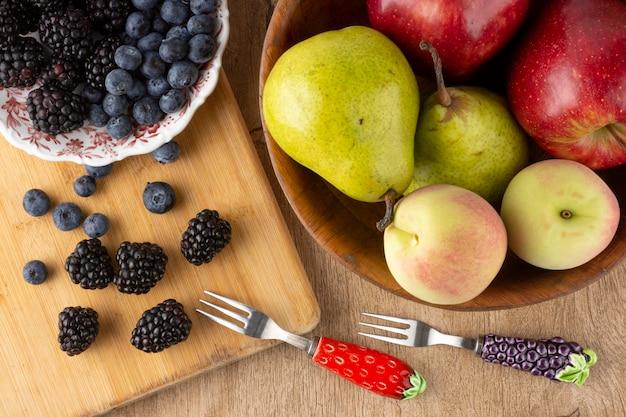 Vista superior de frutas em uma tigela e bagas em um prato sobre uma tábua de madeira, sobre uma mesa de madeira.