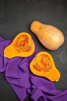 Vista superior de frutas fatiadas de abóbora fresca no chão escuro