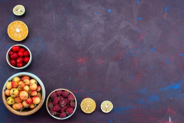 Vista superior de frutas frescas, ameixas e framboesas dentro de pratos na superfície escura