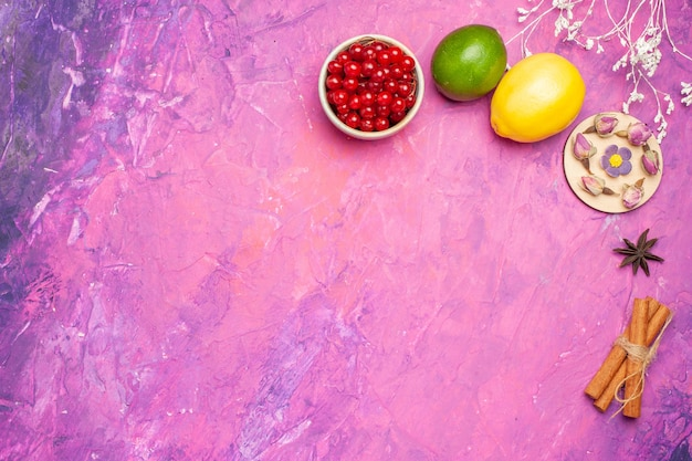 Vista superior de frutas frescas com bagas vermelhas na superfície rosa