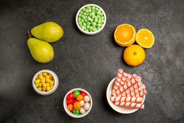 Vista superior de frutas frescas com doces em cinza escuro