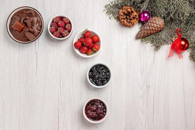 Vista superior de frutas frescas com geleias e sobremesa de chocolate na mesa branca