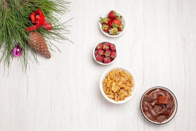 Vista superior de frutas frescas com passas e sobremesa de chocolate na mesa branca