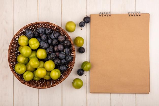 Vista superior de frutas frescas, como abrunhos roxos escuros e ameixas cereja verdes em um balde em um fundo branco com espaço de cópia