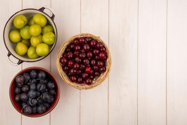 Vista superior de frutas frescas, como ameixas verdes em uma tigela com cerejas vermelhas em uma cesta com abrunhos roxos escuros em uma tigela vermelha em um fundo branco de madeira com espaço de cópia