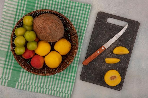 Vista superior de frutas frescas, como cereja verde, pêssego fresco, coco em um balde com fatias de pêssego em uma tábua de cozinha com uma faca em um fundo branco