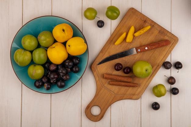 Vista superior de frutas frescas, como cereja verde, pêssegos e abrunhos frescos em uma tigela azul com fatias de pêssego em uma placa de cozinha de madeira com paus de canela com faca em um fundo branco de madeira