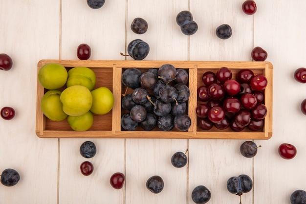 Vista superior de frutas frescas, como cerejas verdes emplumadas e abrunhos roxos escuros em uma bandeja de madeira dividida em um fundo branco de madeira