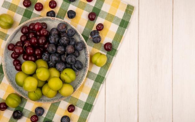 Vista superior de frutas frescas, como cherriessloes e ameixas de cereja verdes em uma tigela sobre uma toalha de mesa quadriculada em um fundo branco com espaço de cópia
