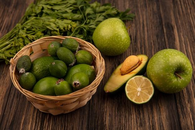 Vista superior de frutas frescas como feijoas e limas em um balde com metade do abacate e limão com maçãs e salsa isoladas em uma superfície de madeira