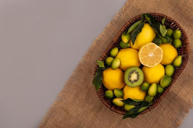 Vista superior de frutas frescas, como kinkans de kiwi e limões em um balde em um pano de saco em uma parede cinza com espaço de cópia