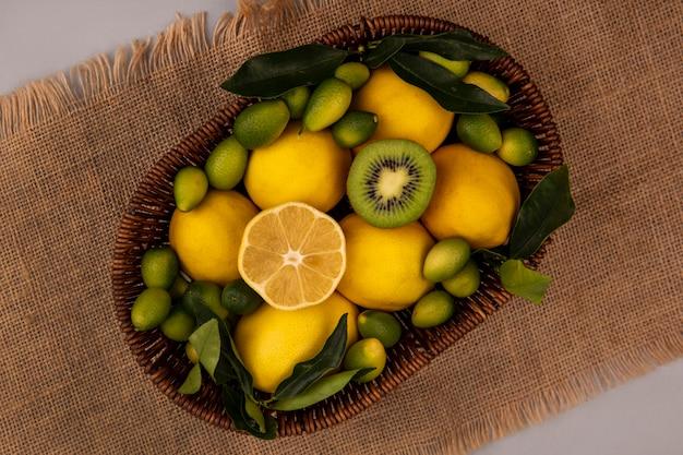 Vista superior de frutas frescas, como kinkans de kiwi e limões em um balde em um pano de saco em uma parede cinza