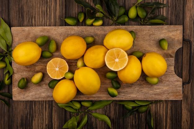 Vista superior de frutas frescas, como kinkans e limões em uma placa de cozinha de madeira em uma parede de madeira
