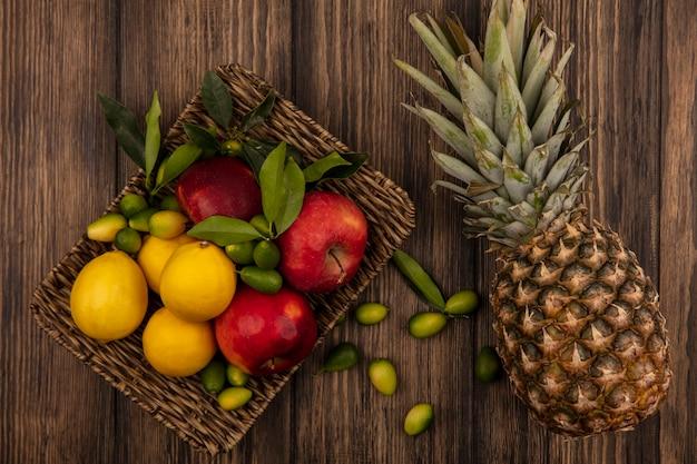 Vista superior de frutas frescas, como maçãs, limões e kinkans em uma bandeja de vime com abacaxi isolado em uma parede de madeira