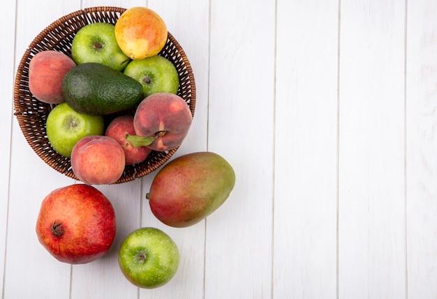 Vista superior de frutas frescas, como maçãs, pêssegos, pêras no balde com manga romã isolada no branco