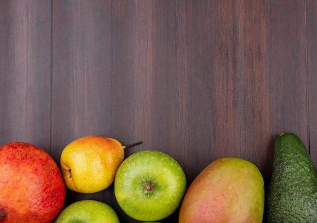 Vista superior de frutas frescas, como manga, maçã, romã, pêra, isolada na madeira