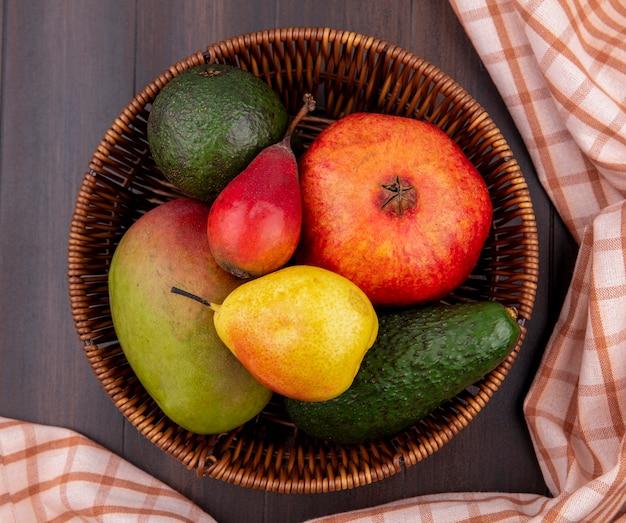 Vista superior de frutas frescas, como pera, limão e manga, romã em um balde com toalha de mesa xadrez na madeira