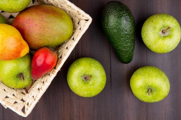 Vista superior de frutas frescas, como pera maçã manga no balde com maçãs verdes na madeira