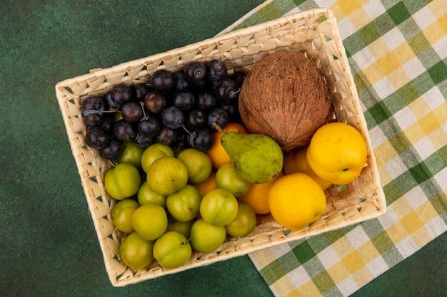 Vista superior de frutas frescas, como pêssegos verdes perolados e coco em um balde sobre um fundo verde