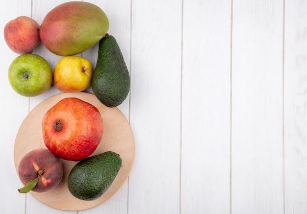 Vista superior de frutas frescas, como romã de pêssego na mesa de cozinha de madeira com abacate de maçã e manga isolado no branco