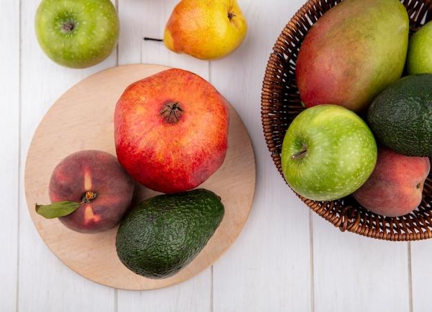 Vista superior de frutas frescas, como romã de pêssego, na mesa de madeira da cozinha com um balde de frutas e maçãs, pêssegos isolados no branco