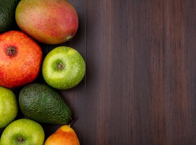 Vista superior de frutas frescas, como romã, maçã, manga na madeira com espaço de cópia