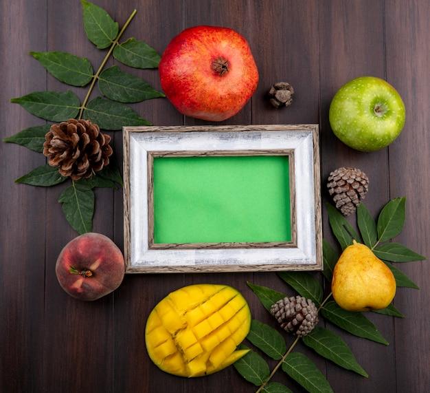 Vista superior de frutas frescas, como romã maçã verde pera fatiada manga isolada com folha e pinhas na madeira