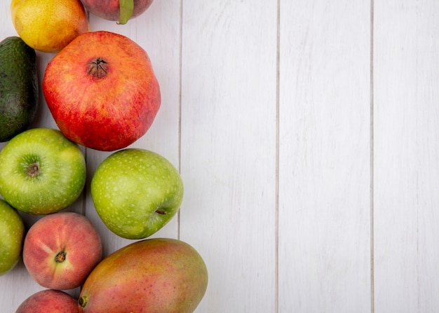 Vista superior de frutas frescas, como romã, maçãs, peras, manga, isolada no branco