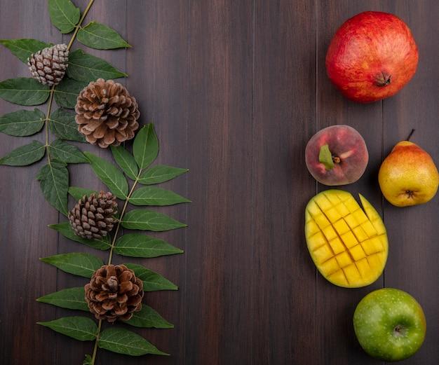 Vista superior de frutas frescas, como romã, pêssego, fatias de manga, maçã, pera, isolada na madeira